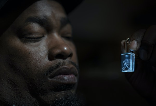 Aubrey Wright held a crystal keychain pendant with a photo of his late son Daunte.