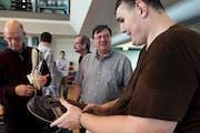 Igor Vovkovinskiy, right, spoke with Trevor Kirby, center, a shoe engineer, at Reebok headquarters, in Canton, Mass. in 2012. Reebok gave him a custom