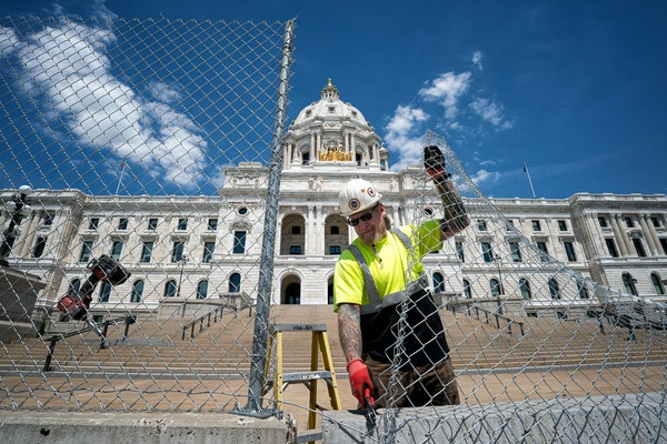 A worker earlier this year removed some of the 2,300 feet of chain link fence that had protected the State Capitol since the civil unrest of 2020.