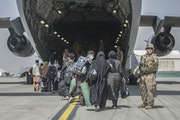 Generic caption on troops withdrawal caused criticism....  In this image provided by the U.S. Marine Corps, families begin to board a U.S. Air Force B