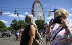 Fairgoers walked near the Great Big Wheel as the daily parade at the Minnesota State Fair took place behind them Tuesday afternoon.