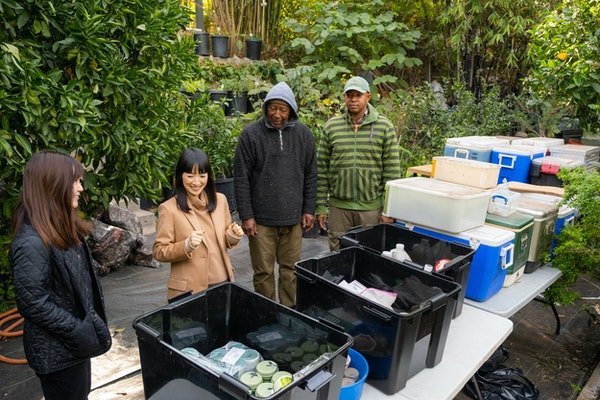 Marie Kondo, second from left, works with Jimmy, second from right, and Logan, right, a father and son who own an organic plant and garden design busi