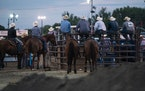 A bunch of cowboys on the sidelines watched the rodeo on the first night of the Hamel Rodeo in Hamel, Minn., on Thursday, July 8, 2021.
