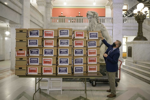 Minneapolis City Clerk Casey Carl reached for one of 30 boxes, containing more than 20,000 signed petitions, that call for replacing the Minneapolis P