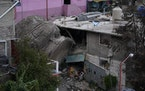 A boulder that plunged from a mountainside rests among homes in Tlalnepantla, on the outskirts of Mexico City, when a mountain gave way on Friday, Sep