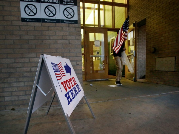 As the polls were about to open for the day at the Brian Coyle Center an election worker who wished to not be identified walked to place a flag outsid