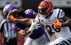 Cincinnati Bengals running back Joe Mixon (28) knocked the helmet off Minnesota Vikings middle linebacker Eric Kendricks (54) as he rushed the ball in