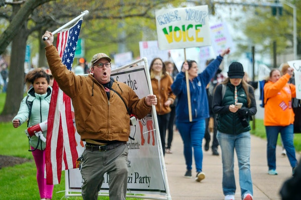 In this April 27, 2021 file photo, opponents of a bill to repeal Connecticut's religious exemption for required school vaccinations march down Capit