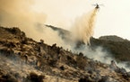 A helicopter drops water on the KNP Complex Fire burning along Generals Highway in Sequoia National Park, Calif., on Wednesday, Sept. 15, 2021. The bl