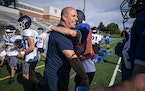 Steve Rosga, a strength and conditioning coach and physical education teacher at St. Thomas Academy, was greeted by wide receiver Luke Dobbs during fo