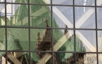 Minneapolis City Hall is reflected in the windows of the Hennepin County Government Center.