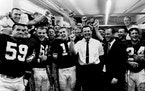Coach Norm Van Brocklin, in white shirt, leads a Viking victory yell as general manager Bert Rose joins in.