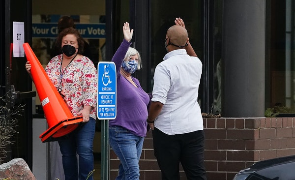 Elliott Payne, the first voter and a candidate for City Council Ward 1, right, gave a high five to fellow voter Jill Davis, the second voter, during t