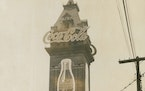 """The tower of the old Exposition Building featured neon-lit, 54-foot bottles of Coke beneath the word """"Coca-Cola"""" in 16-foot script lettering."""
