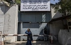 An Afghan man walks past the former Women's Affairs Ministry building in Kabul, Afghanistan, Saturday, Sept. 18, 2021. Afghanistan's new Taliban r