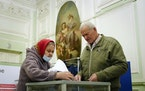 People cast their ballots during the State Duma, the Lower House of the Russian Parliament and local parliaments elections at a polling station situat