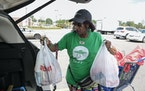In this file photo, Shipt worker Gina Moorman loads grocery to her car after she finishes shopping for a customer at Meijer in Detroit.