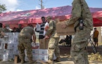 Members of the National Guard help distribute military field rations, known as MRE, at Treme Recreation Community Center in New Orleans on Wednesday,