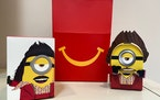 """A cardboard McDonald's Happy Meal toy is shown with a Happy Meal box on Sept. 20, 2021. McDonald's plans to """"drastically"""" reduce the plastic i"""