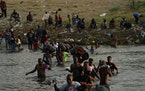 Migrants, many from Haiti, wade across the Rio Grande from Del Rio, Texas, to return to Ciudad Acuna, Mexico, Tuesday, Sept. 21, 2021, to avoid deport