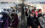 Travelers aboard a fully booked Jet Blue flight from Ronald Reagan Washington National Airport to Orlando, Fla., on Feb. 24, 2021.