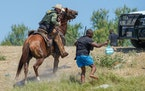 A U.S. Border Patrol agent on horseback uses the reins to try and stop a Haitian migrant from entering an encampment on the banks of the Rio Grande ne