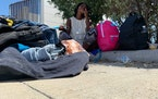 Junia Michel, 25, hides from the Texas sun outside at a bus stop in Del Rio, Texas, Monday, Sept. 20, 2021. The Haitian migrant, who is seven months p