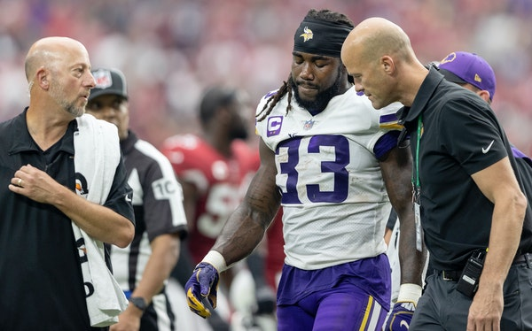 Vikings running back Dalvin Cook (33) walked off the field with trainers during Sunday's game in Arizona.