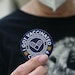 A woman holds up a sticker after getting her third dose of the COVID-19 vaccine at a clinic in Pasadena, California.