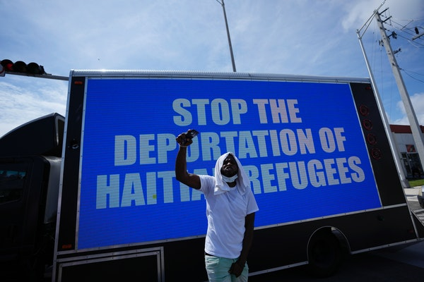 """A man chants in front of a billboard truck reading """"Stop the Deportation of Haitian Refugees,"""" as members of Miami's Haitian community protest a"""