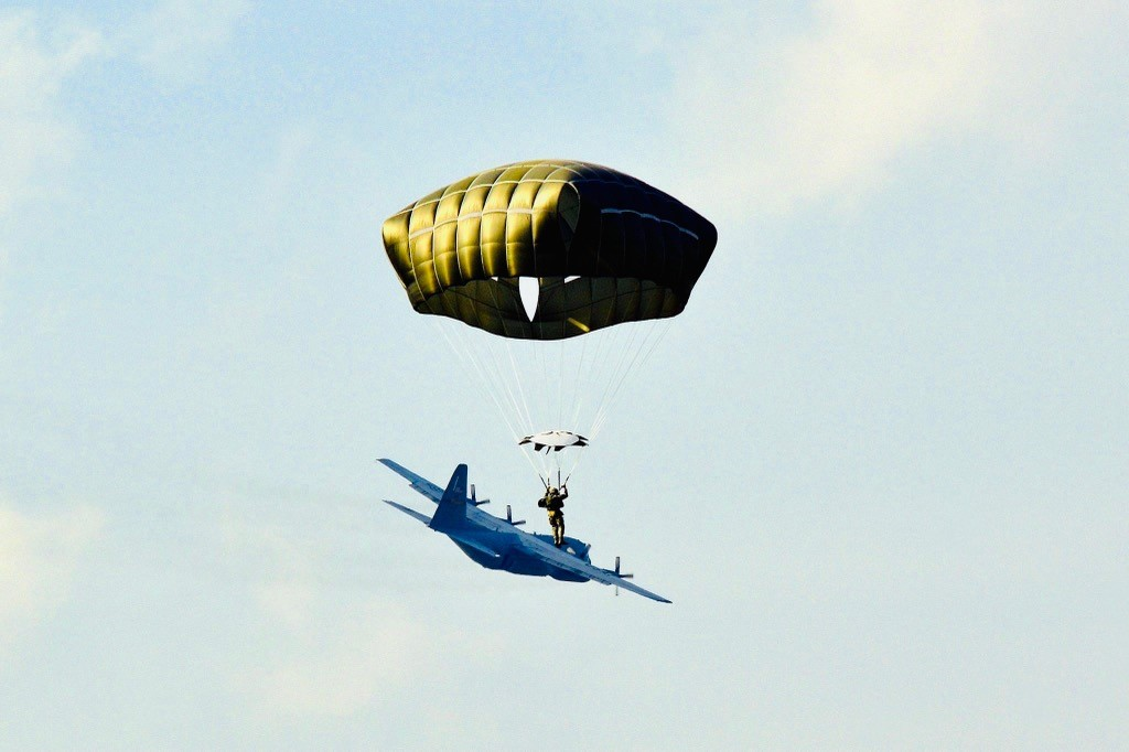 A member of the Minnesota National Guard parachutes out of a C-130 aircraft during a training exercise.