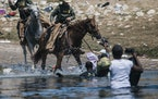 U.S. Customs and Border Protection mounted officers attempt to contain migrants as they cross the Rio Grande from Ciudad Acuña, Mexico, into Del Rio,