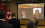A video screen displays images of Canadians Michael Kovrig, left, and Michael Spavor at an event held in connection with the announcement of the sente