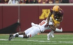 Minnesota Gophers wide receiver Chris Autman-Bell (7) was tackled by Bowling Green Falcons safety Jordan Anderson (0) in the first quarter.