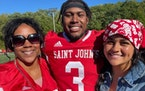 Ravi Alston, a St. John's star as receiver Saturday, with mom Tyrisa & girlfriend Kiana Reedy on the field afterSaturday's game.