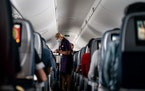 Flight attendants hand out refreshments to a packed Delta Air Lines flight on Friday, May 21, 2021. Delta wants all air carriers to share no-fly lists