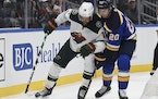 The Blues' Brandon Saad (20) and the Wild's Jordan Greenway battled for the puck in the first period of a preseason game.