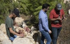 Palestinians inspect a bloodstained site after an Israeli army operation that left some Palestinian men killed, in the West Bank village of Beit Anan,