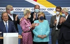 German Chancellor Angela Merkel stands as leading CDU members applaud and Armin Laschet, the top CDU candidate grimaces, after the German parliament e