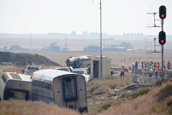 Workers stand near train tracks, Monday, Sept. 27, 2021, next to overturned cars from an Amtrak train that derailed Saturday, near Joplin, Mont., kill