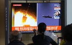 People watch a TV showing a file image of North Korea's missiles launch during a news program at the Seoul Railway Station in Seoul, South Korea, Tu