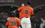Kevin Gausman, rear, celebrated with Brandon Belt (9) after hitting a sacrifice fly that scored Brandon Crawford (35) during a Giants victory in Septe