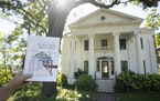 Richard Kronick held up the coloring book in front of its cover subject, an 1851 Greek Revival house in Irvine Park.