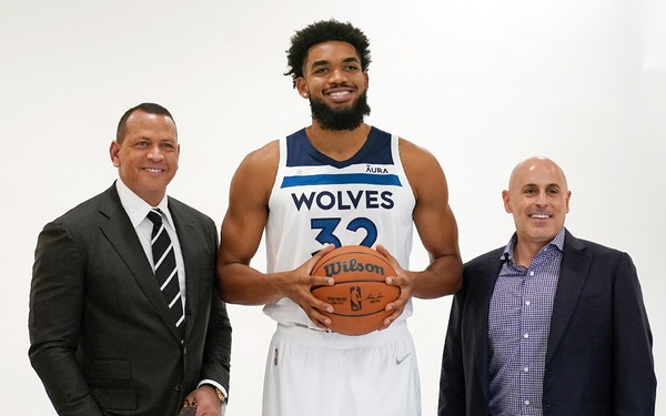 Minnesota Timberwolves' Karl-Anthony Towns, center, poses with new team ownership partners Marc Lore, right, and baseball great Alex Rodriguez, left,