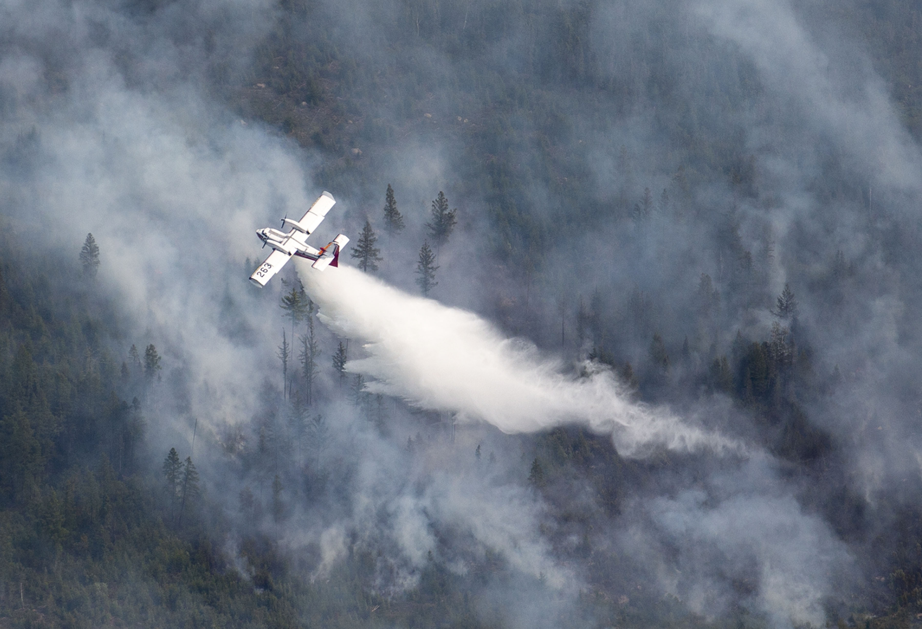 An aircraft drops water scooped from nearby Sand Lake onto the Greenwood Fire in August 2021.