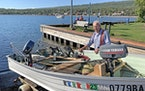 Pete Harris of Grand Marais with the vintage 14-foot boat he uses to fish lake trout on Lake Superior.