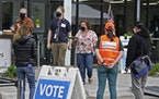 Following the first day of early voting morning rush, poll workers stood outside waiting for more voters at Minneapolis Elections and Voter Services S