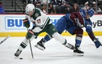 Wild left wing Marcus Foligno gets tangled up with Avalanche defenseman Kurtis MacDermid while driving to the net In the second period