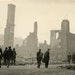 People walking in front of a destroyed school building after the fires of 1918.