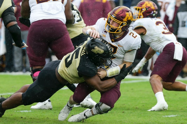 Purdue defensive end George Karlaftis (5) tackles Minnesota quarterback Tanner Morgan (2) during the first quarter of an NCAA college football game, S